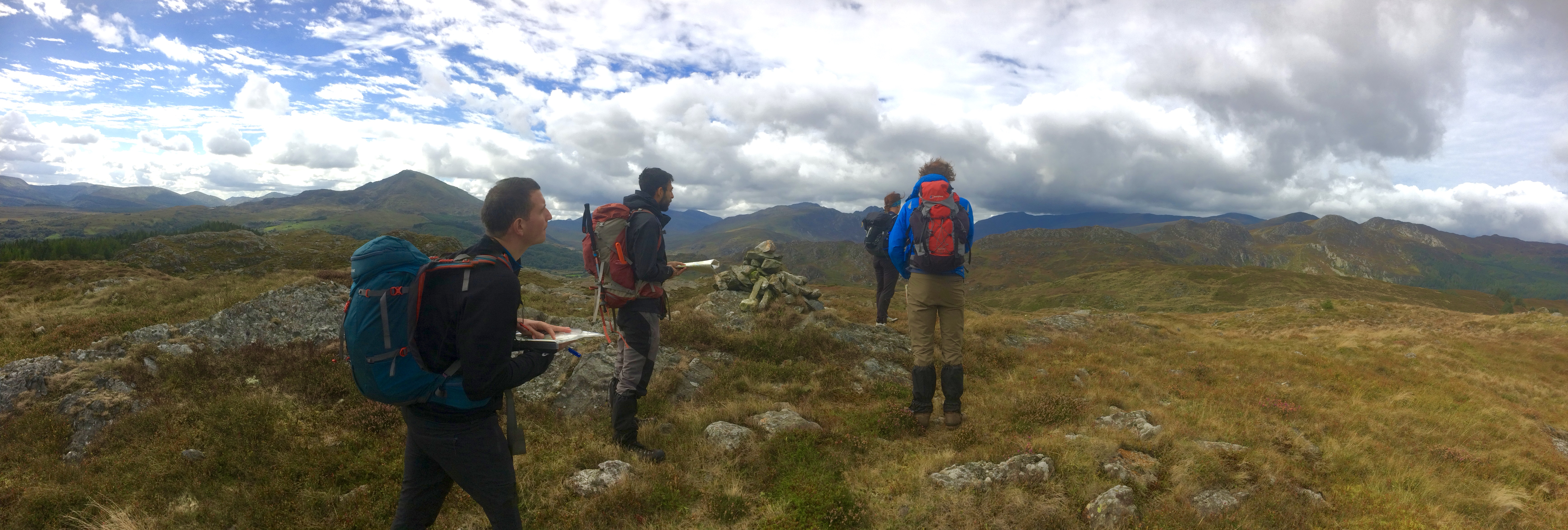 Hillwalkers in Snowdonia with maps and compasses using navigation skills